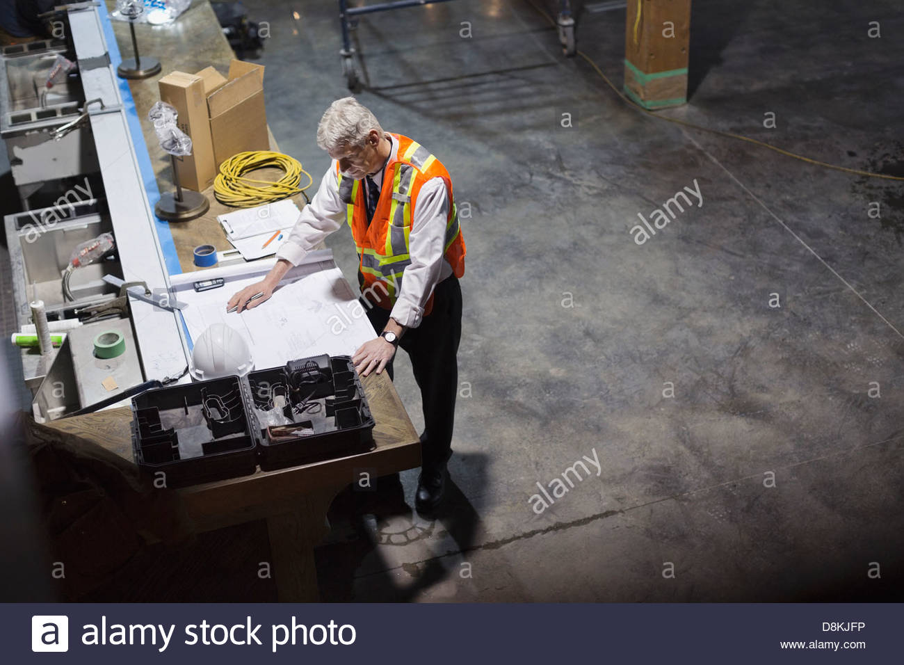 Male architect working on blueprint at construction site - Stock Image