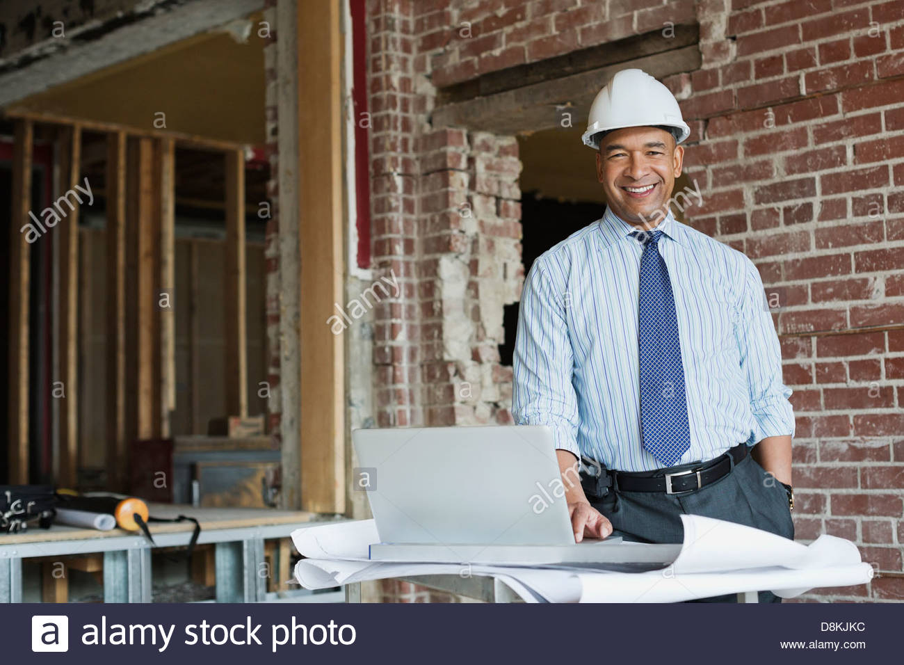 Portrait of male architect with laptop at construction site - Stock Image