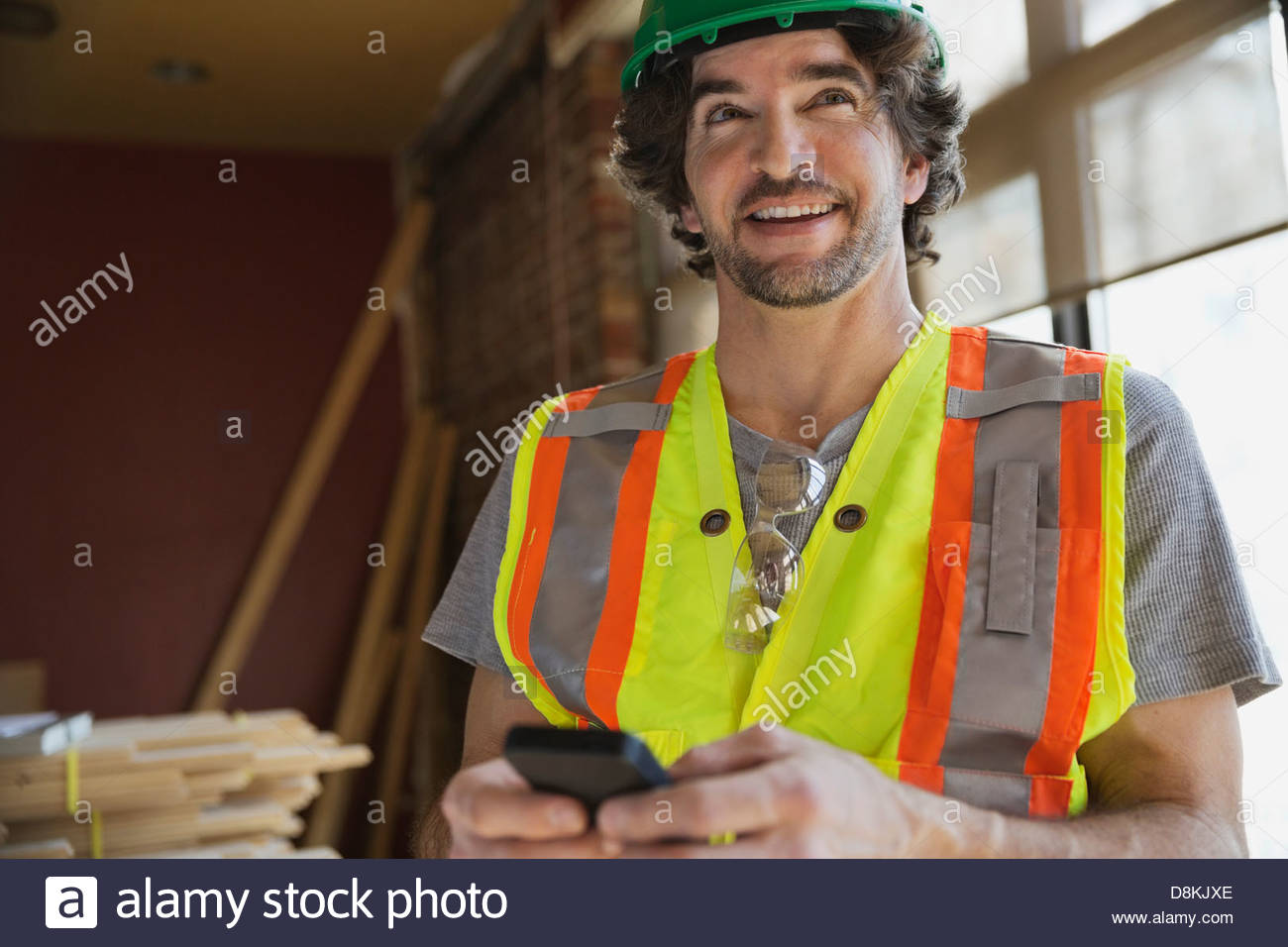 Tradesman using mobile phone at construction site - Stock Image