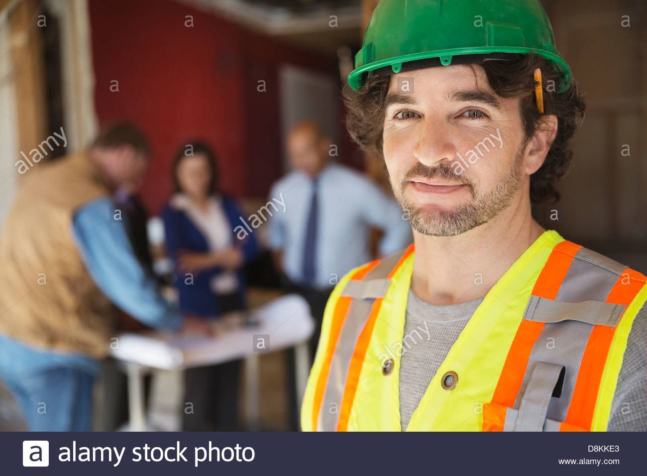 Portrait of tradesman with coworkers at construction site Stock Photo