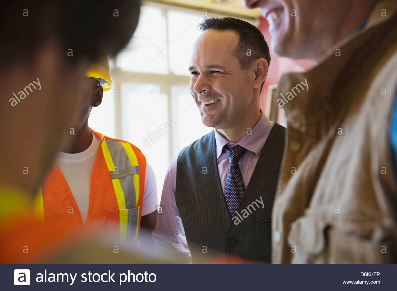 Smiling architect talking with team at construction site - Stock Image