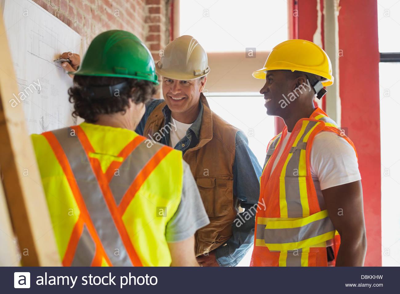 Foreman explaining plan on blueprint to tradesmen at construction site - Stock Image