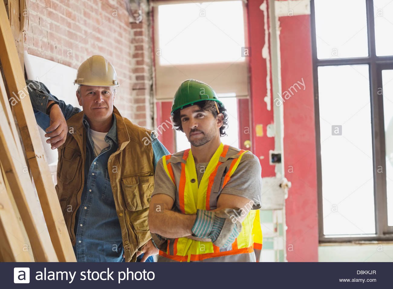 Portrait of tradesman and foreman at construction site - Stock Image