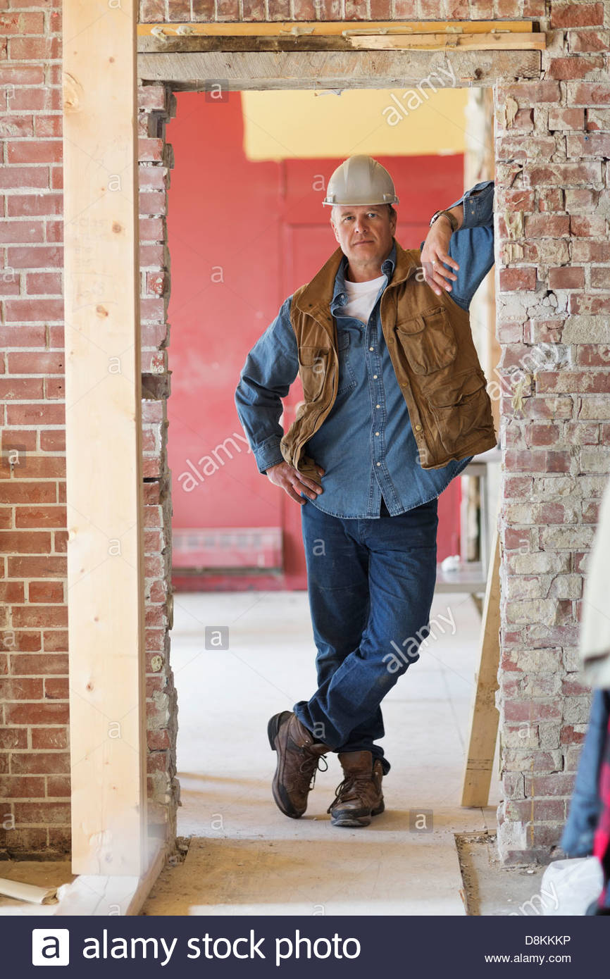 Full length portrait of foreman leaning on brick wall at construction site - Stock Photo