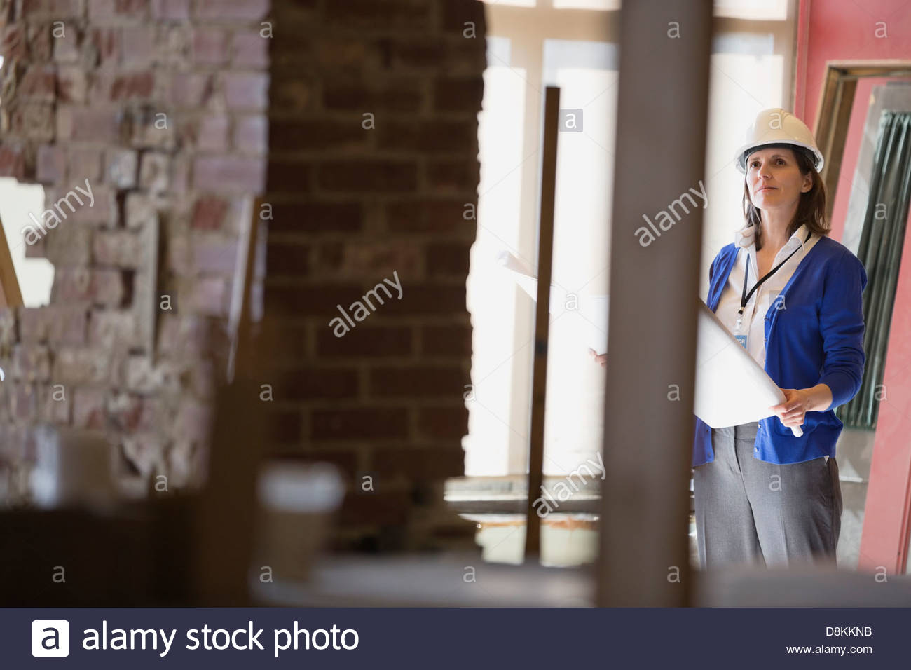 Female architect with blueprint at construction site - Stock Image