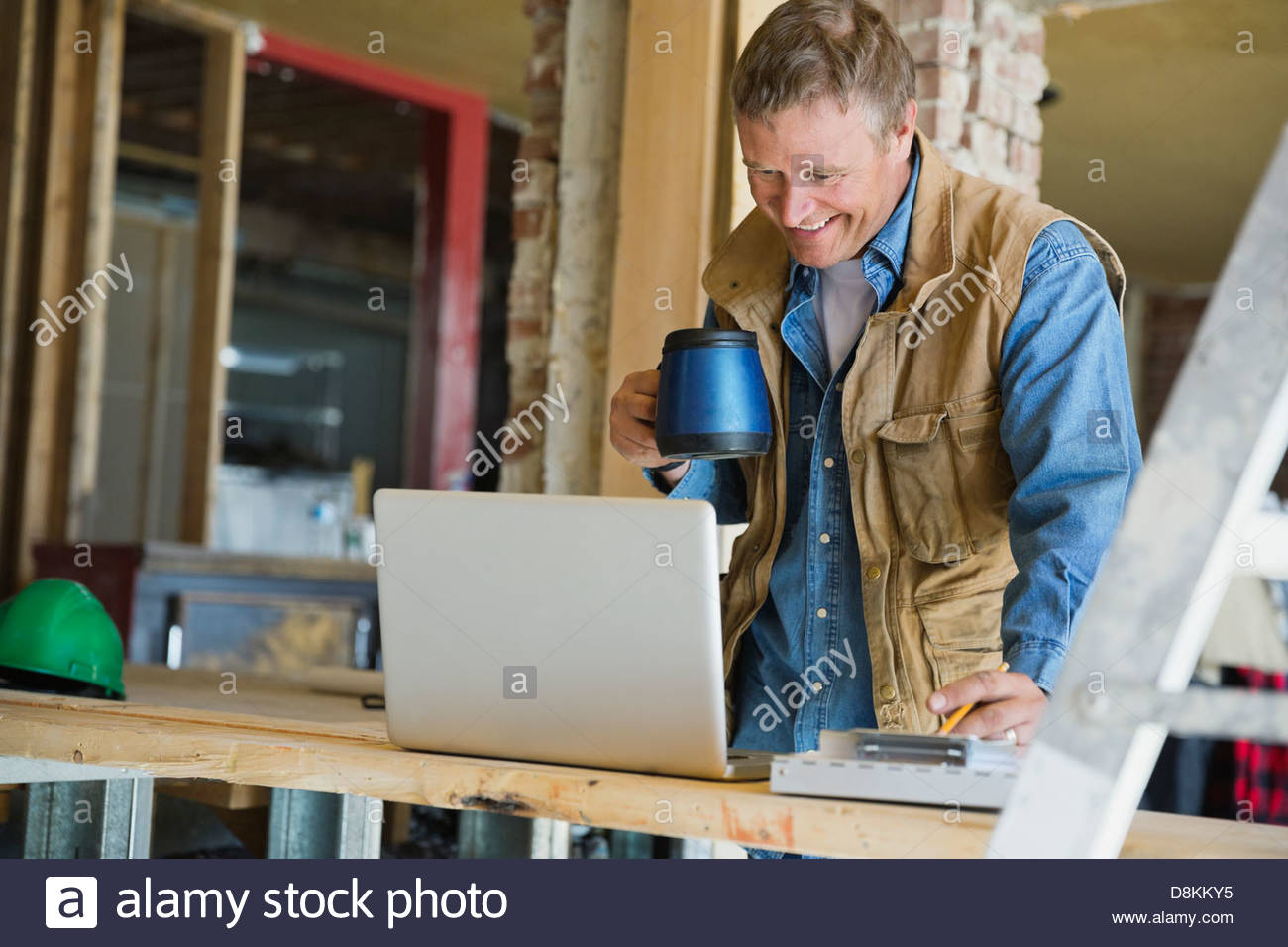 Foreman with coffee looking at laptop at construction site - Stock Image