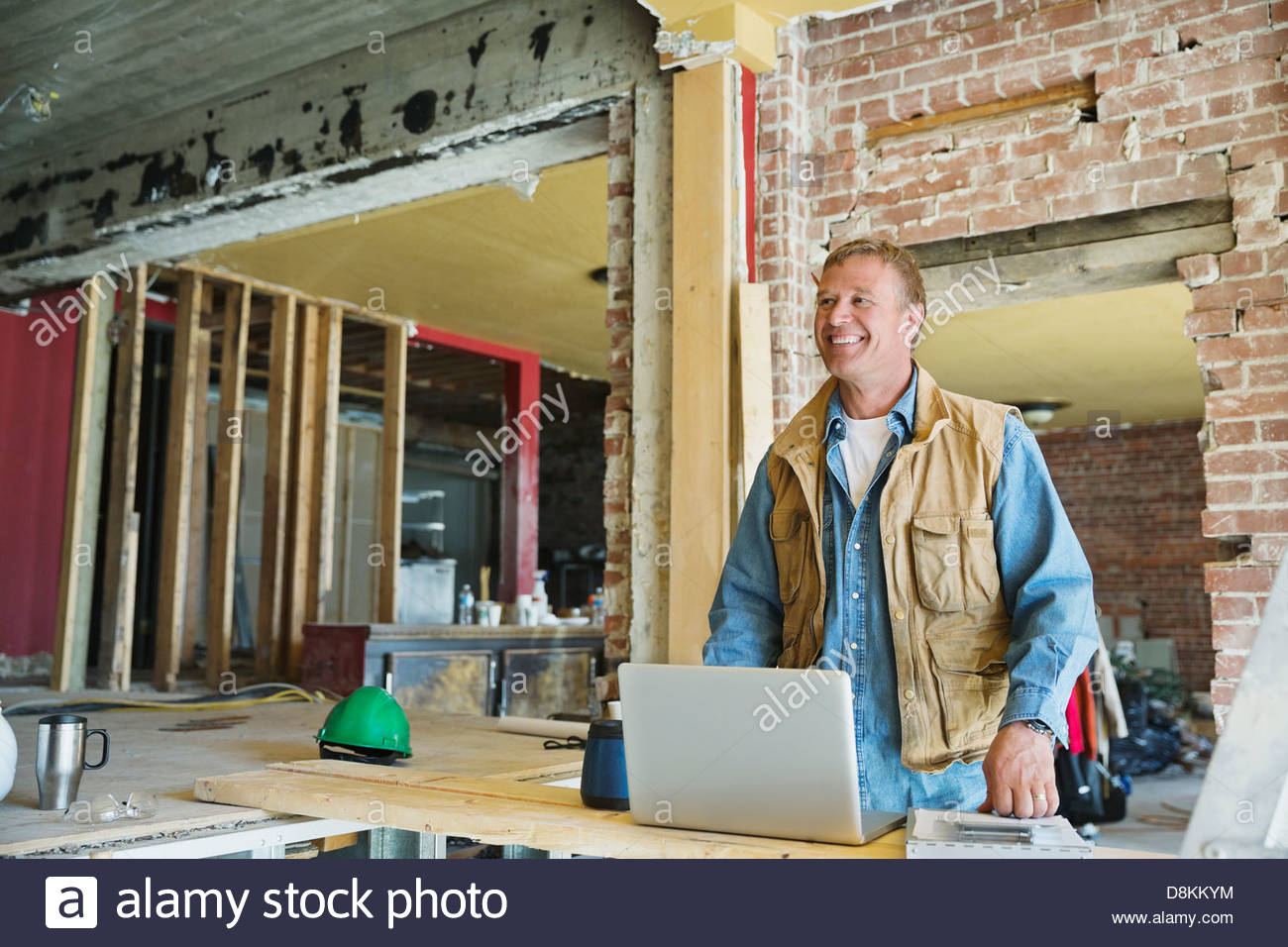 Foreman with laptop at construction site - Stock Image