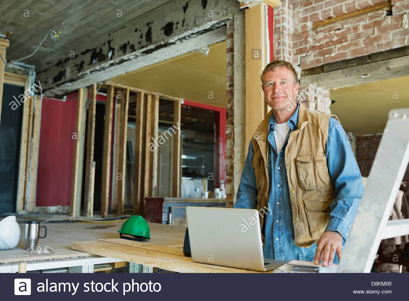 Portrait of foreman with laptop at construction site - Stock Image
