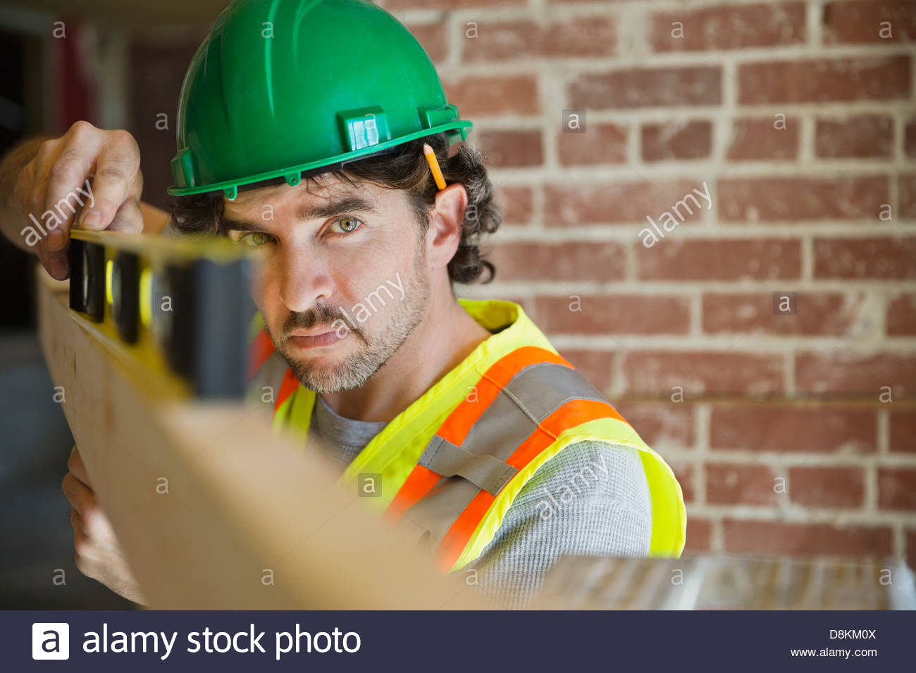 Tradesman leveling wooden plank at construction site Stock Photo