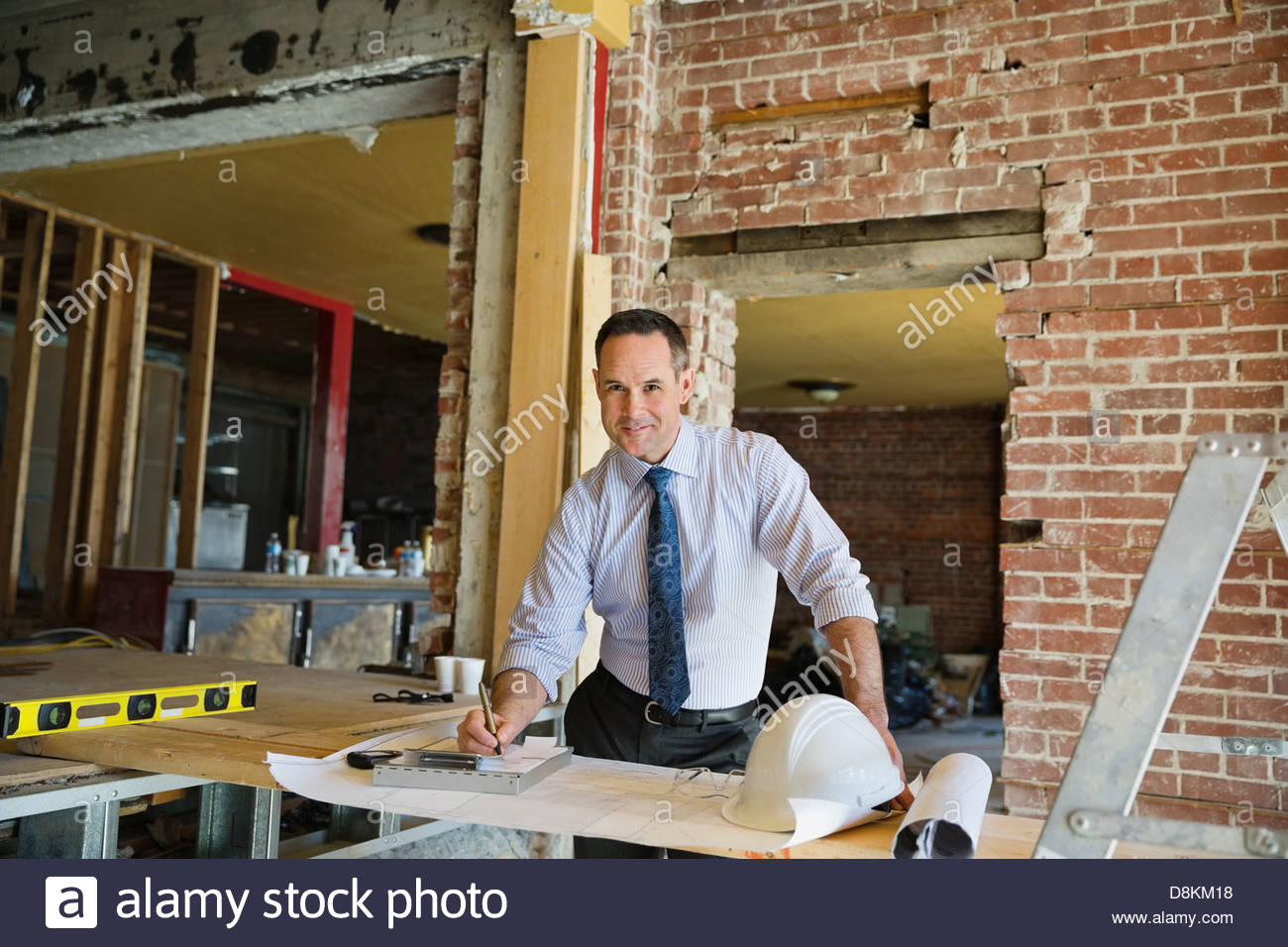 Portrait of male architect writing notes on work order at construction site - Stock Image