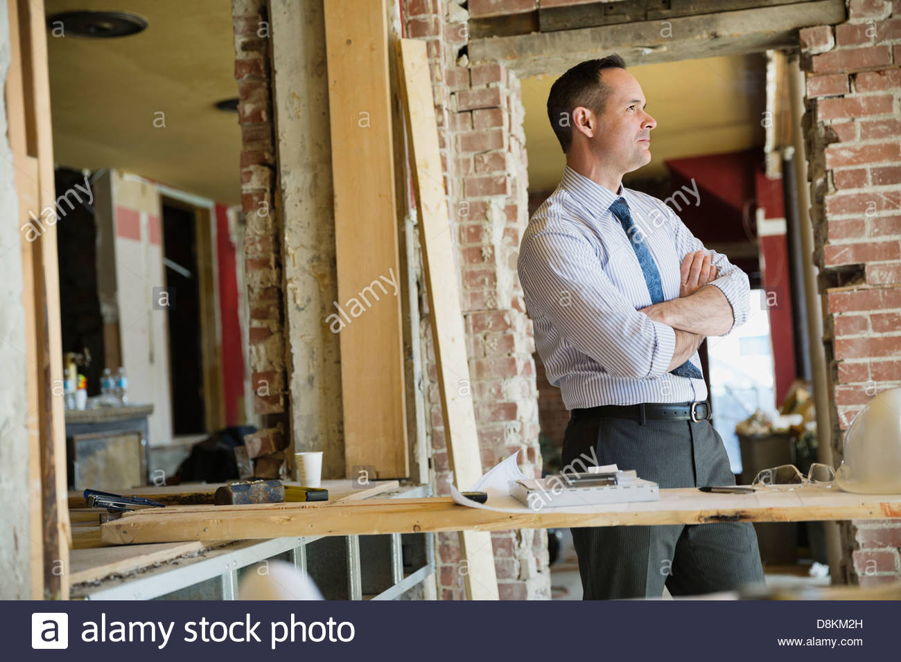 Side view of male architect standing at construction site - Stock Image