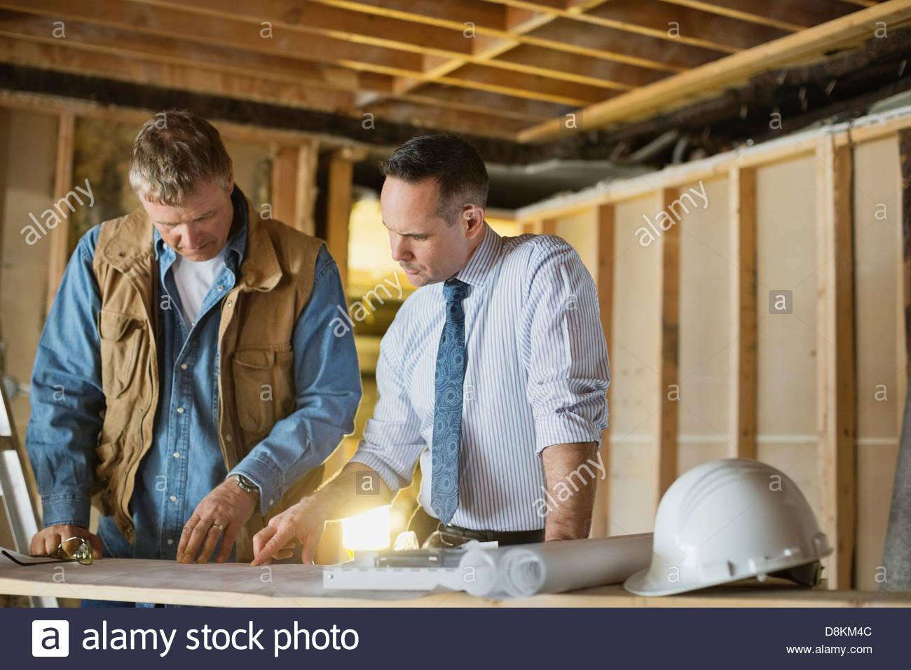 Male architect and foreman discussing blueprint at construction site - Stock Image