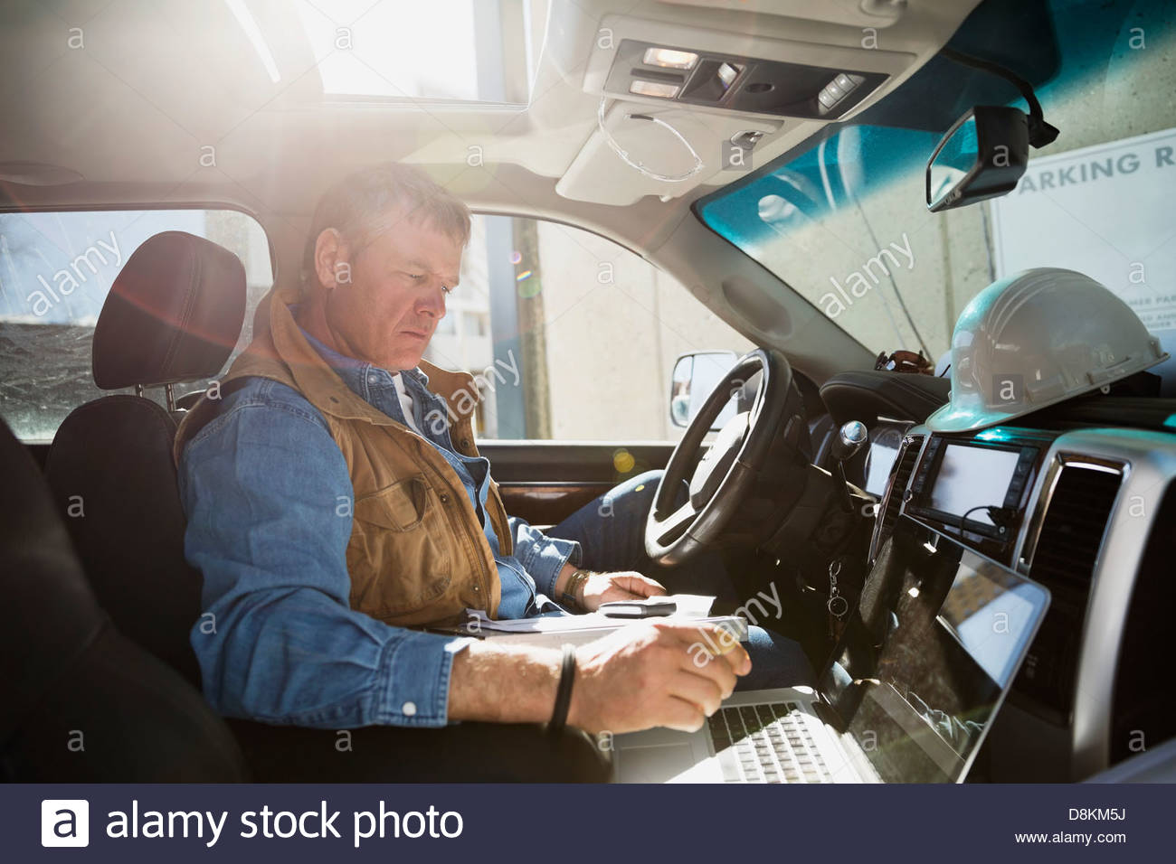 Foreman using laptop in truck - Stock Image