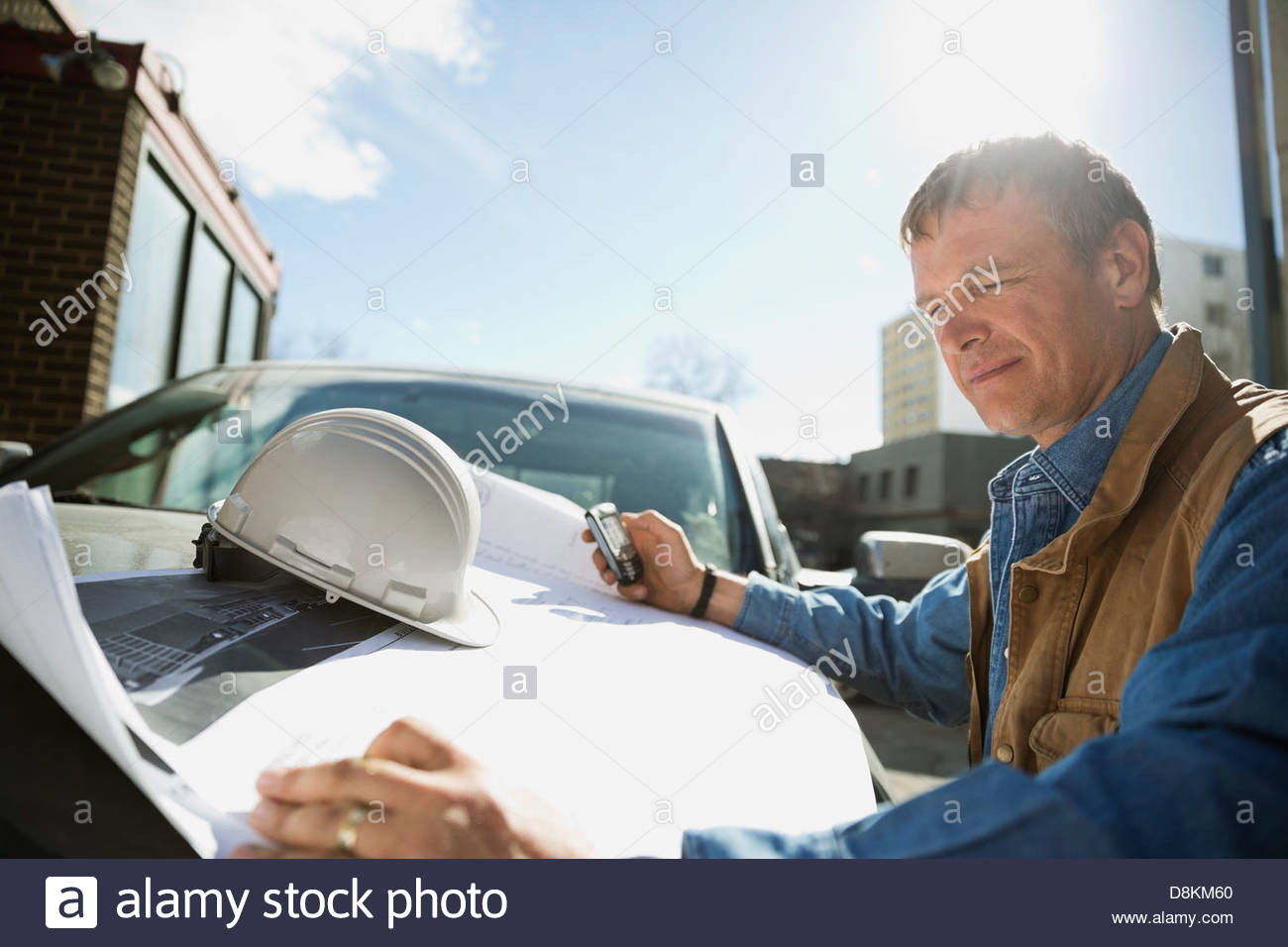 Foreman with mobile phone checking blueprint on truck hood - Stock Image