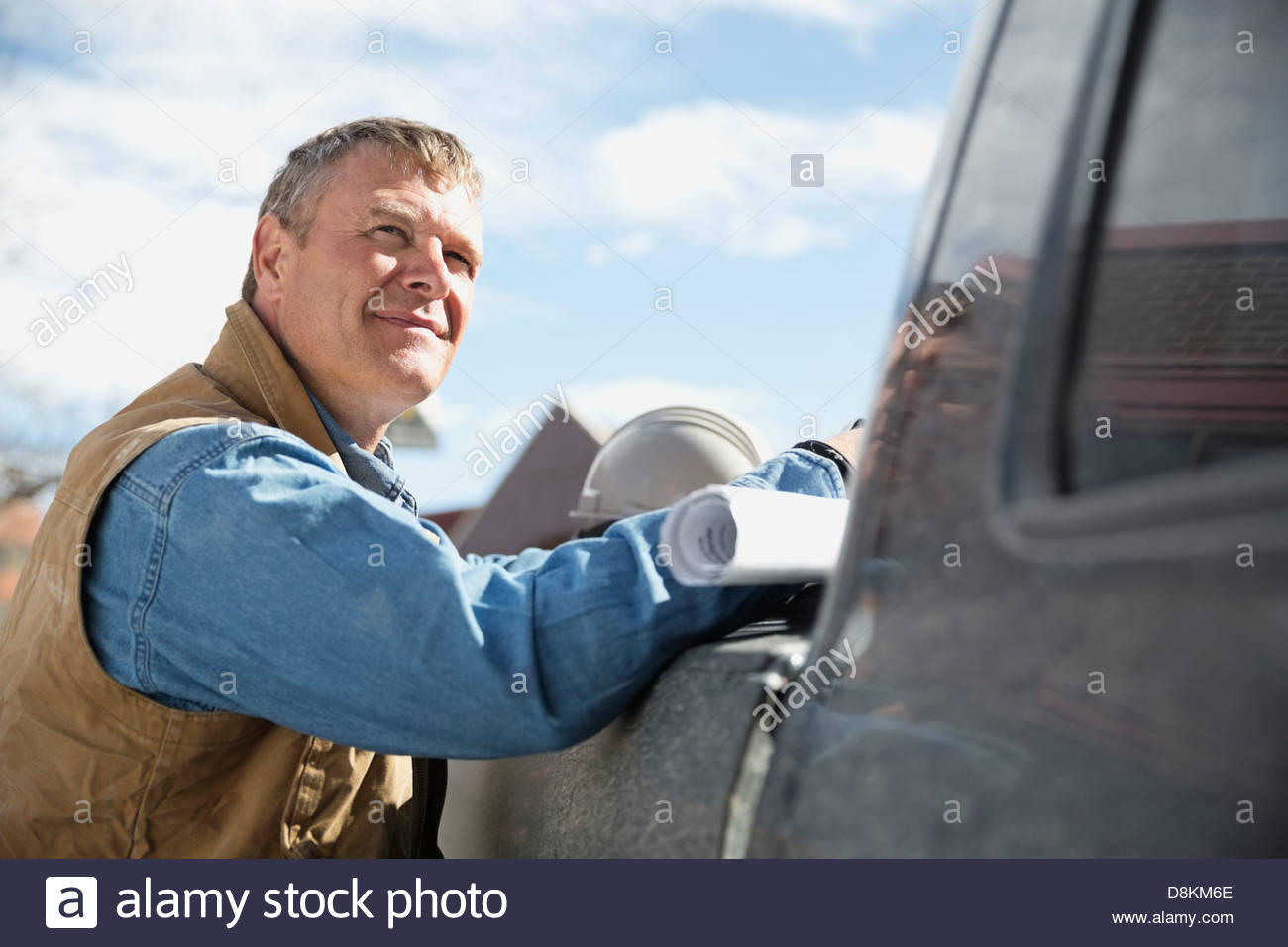 Foreman looking away leaning on truck - Stock Image