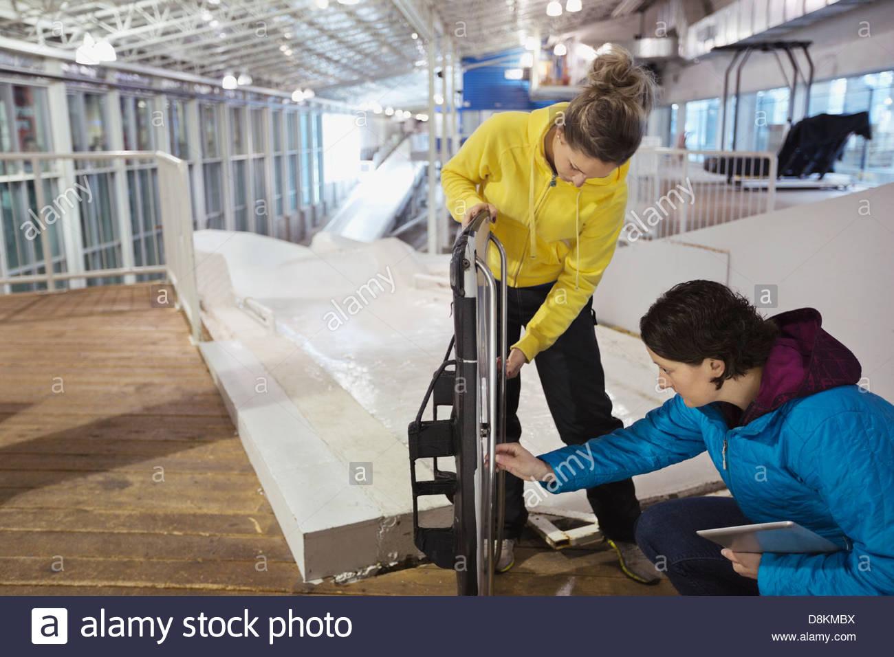 Female skeleton athlete with coach inspecting sled on track - Stock Image