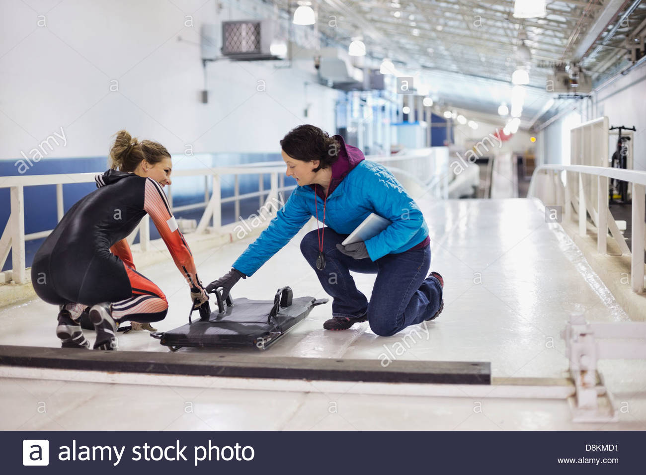 Female coach explaining technique to skeleton athlete - Stock Image