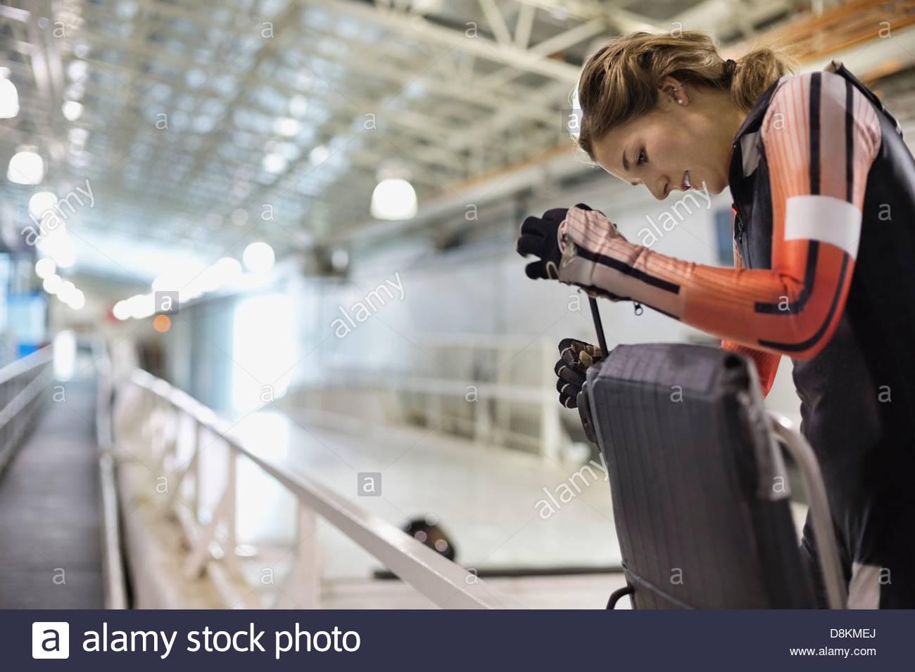 Female skeleton athlete repairing sled on track Stock Photo