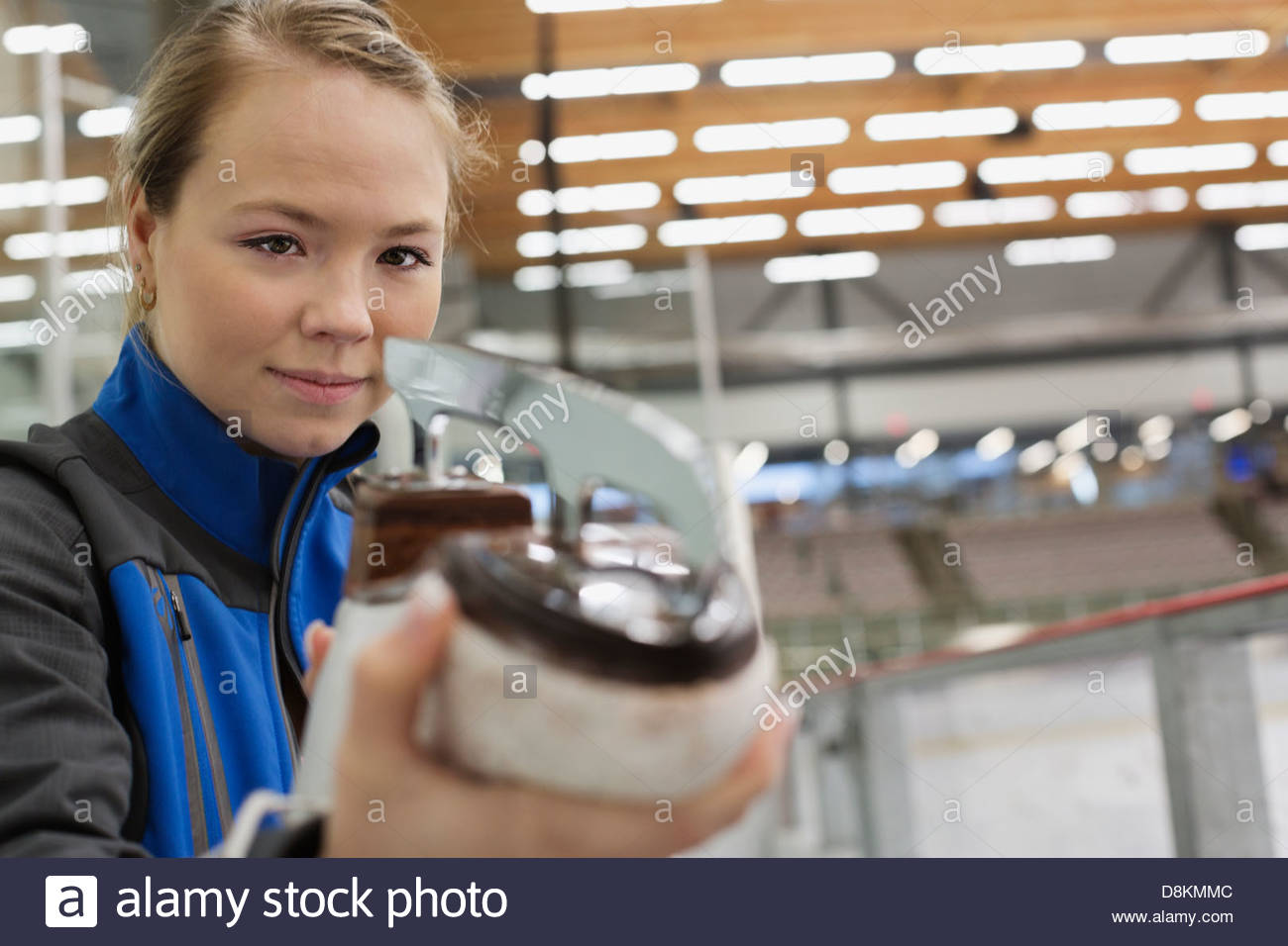 Female figure skater inspecting blades in skating rink - Stock Image