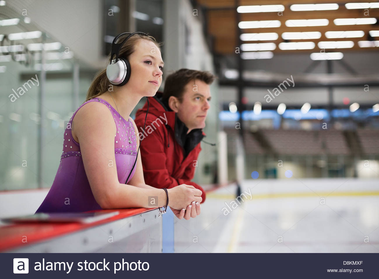 Female figure skater with coach preparing for routine in skating rink - Stock Image