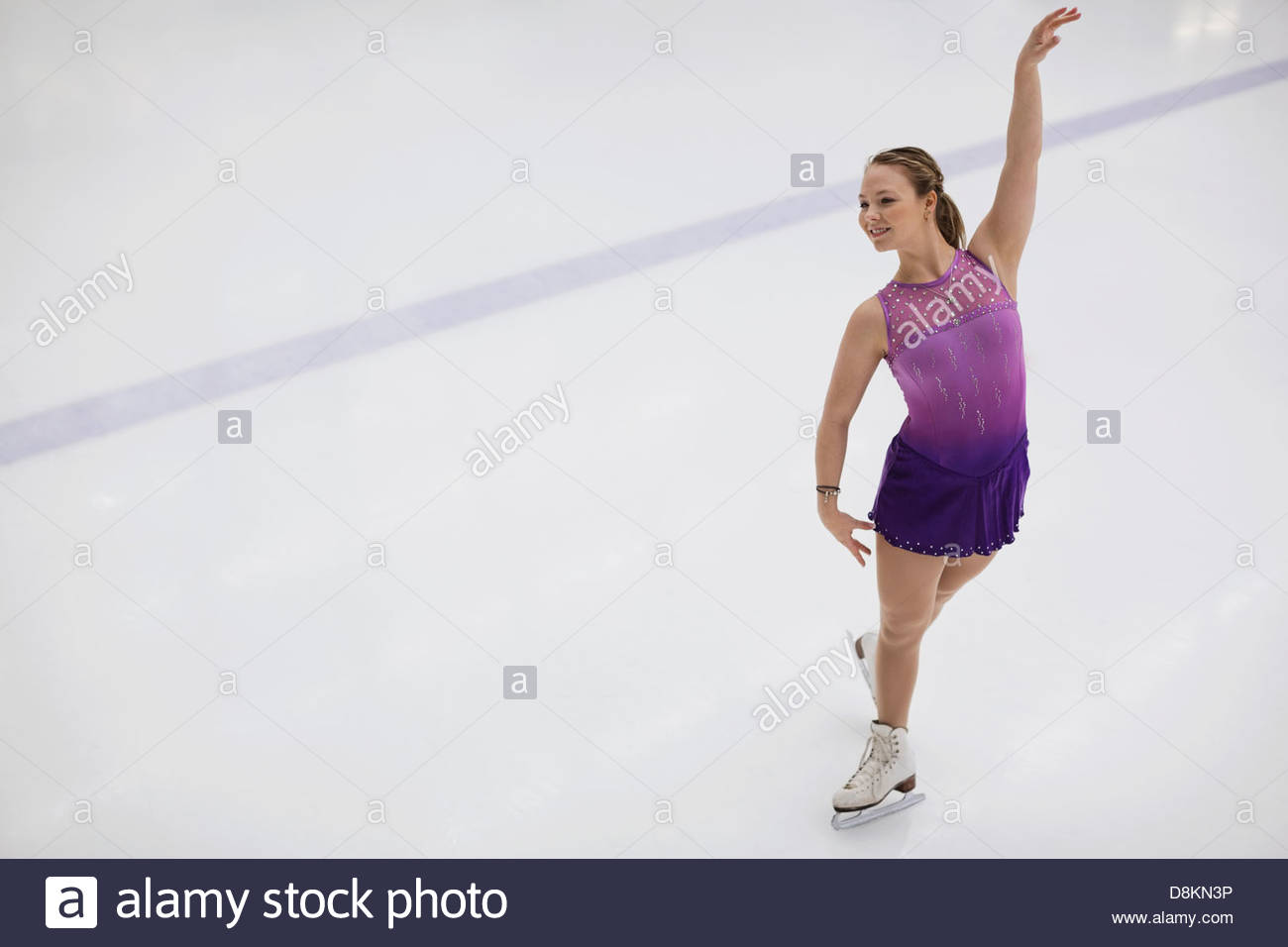 Female figure skater performing routine in skating rink - Stock Image