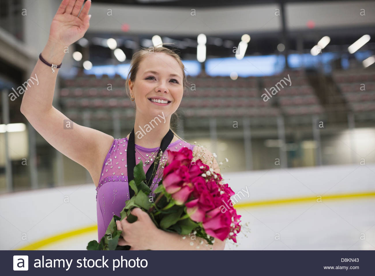 Smiling female figure skater with flowers in skating rink - Stock Image