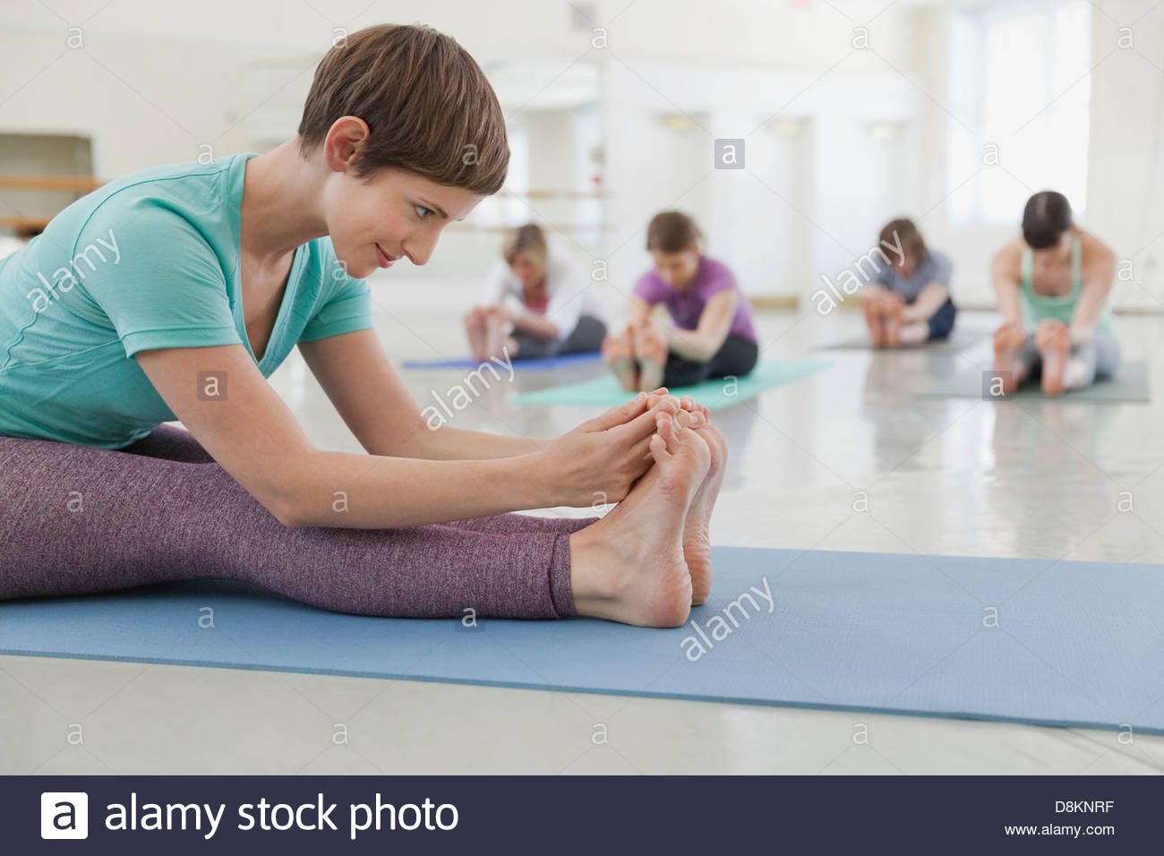 Woman instructor practicing yoga with students in yoga studio - Stock Image