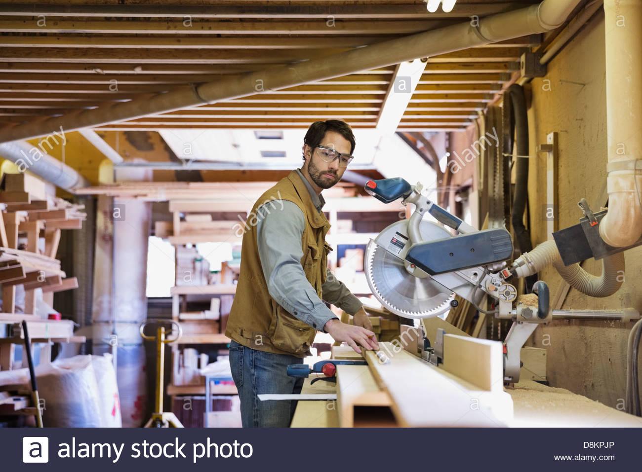 Woodworker measuring wood in workshop - Stock Image