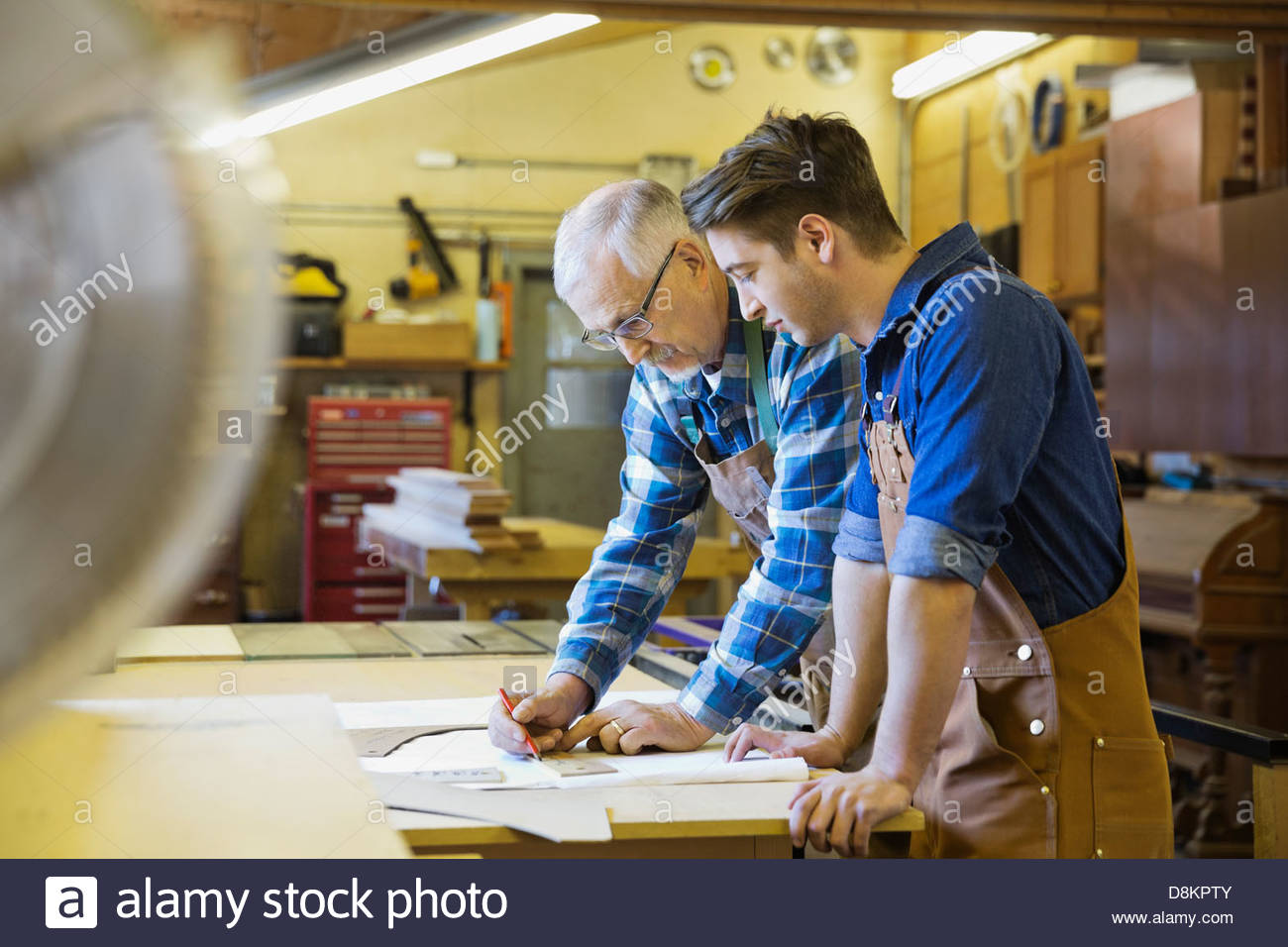 Senior carpenter working with apprentice in workshop - Stock Image