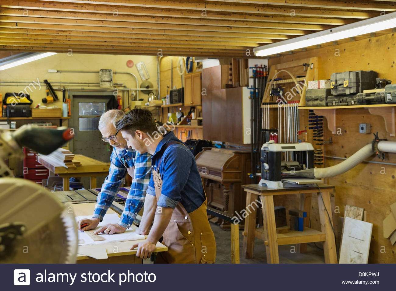 Senior woodworker planning with apprentice - Stock Image
