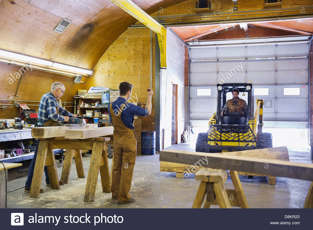 Carpenter driving forklift while coworker guides him - Stock Image