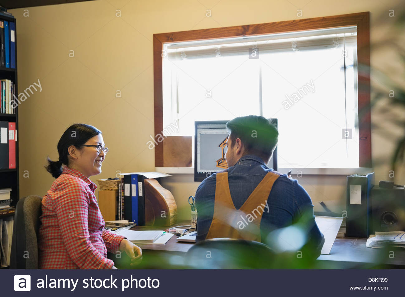 Coworkers discussing CAD drawings on computer screen - Stock Image