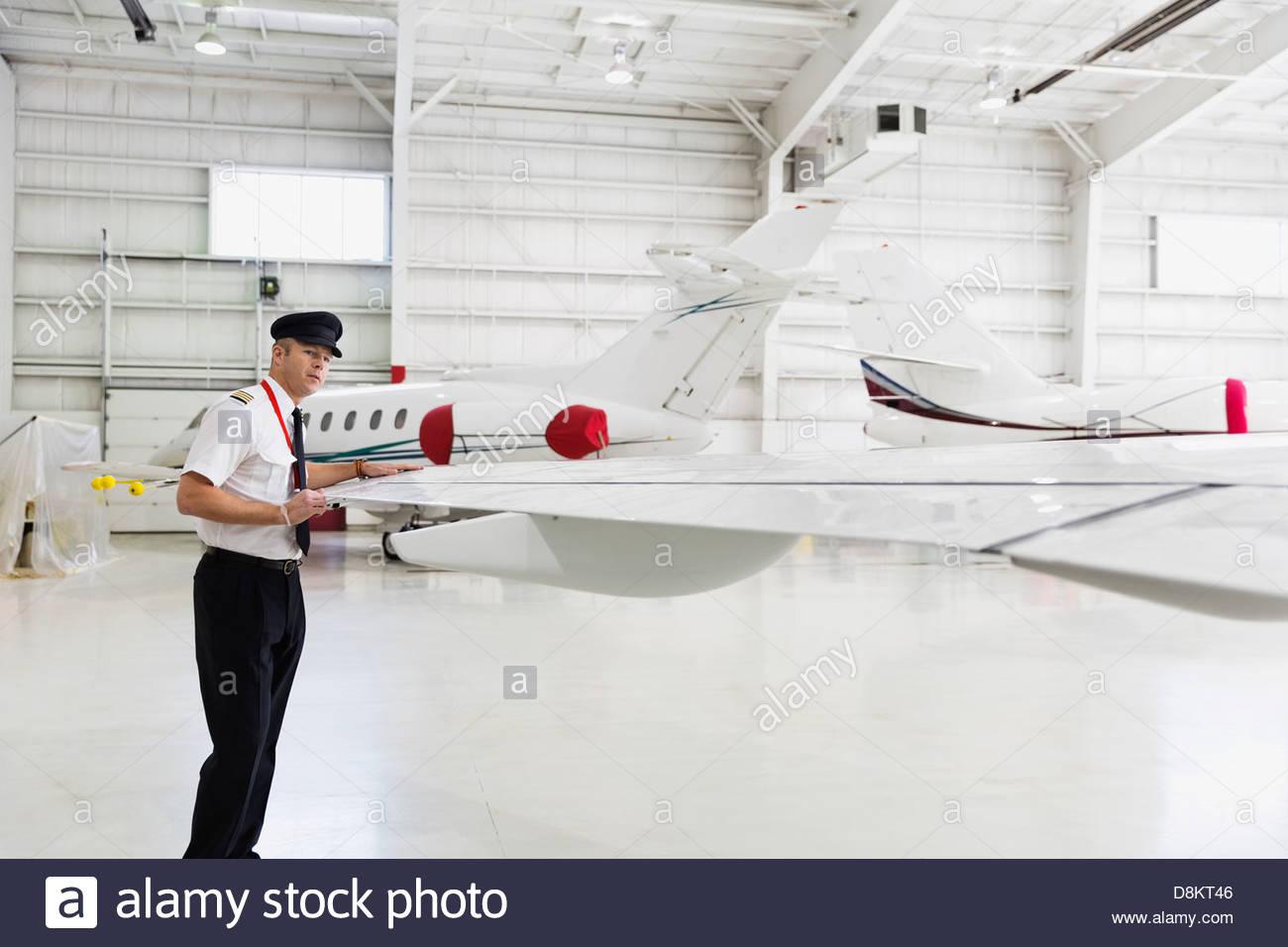 Male pilot checking airplane wing in hangar - Stock Image