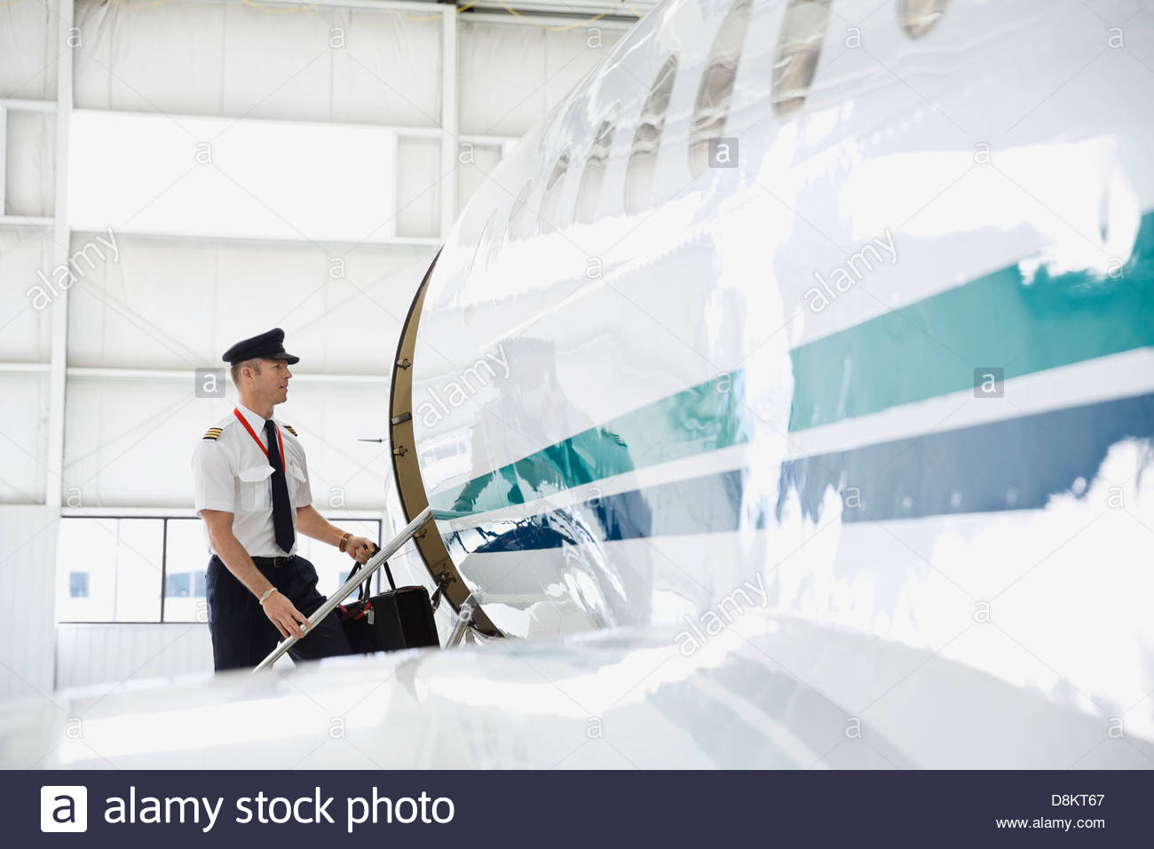 Male pilot boarding plane with luggage in hangar - Stock Image