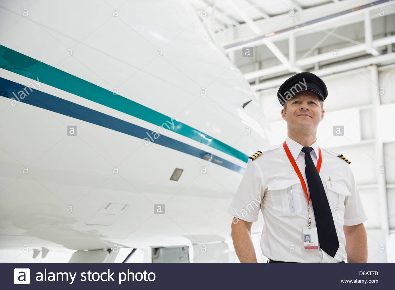 Male pilot standing by airplane in hangar - Stock Image