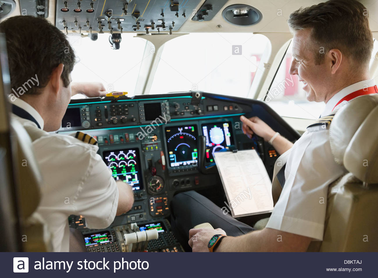 Male pilot and co-pilot checking instrument panel in airplane cockpit - Stock Image