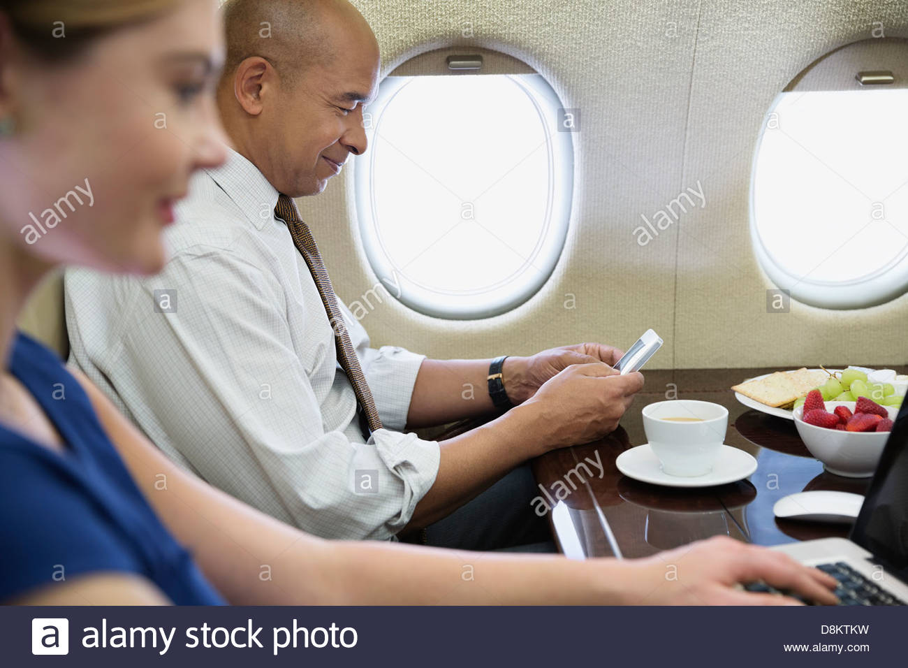 Business colleagues using technology in airplane - Stock Image