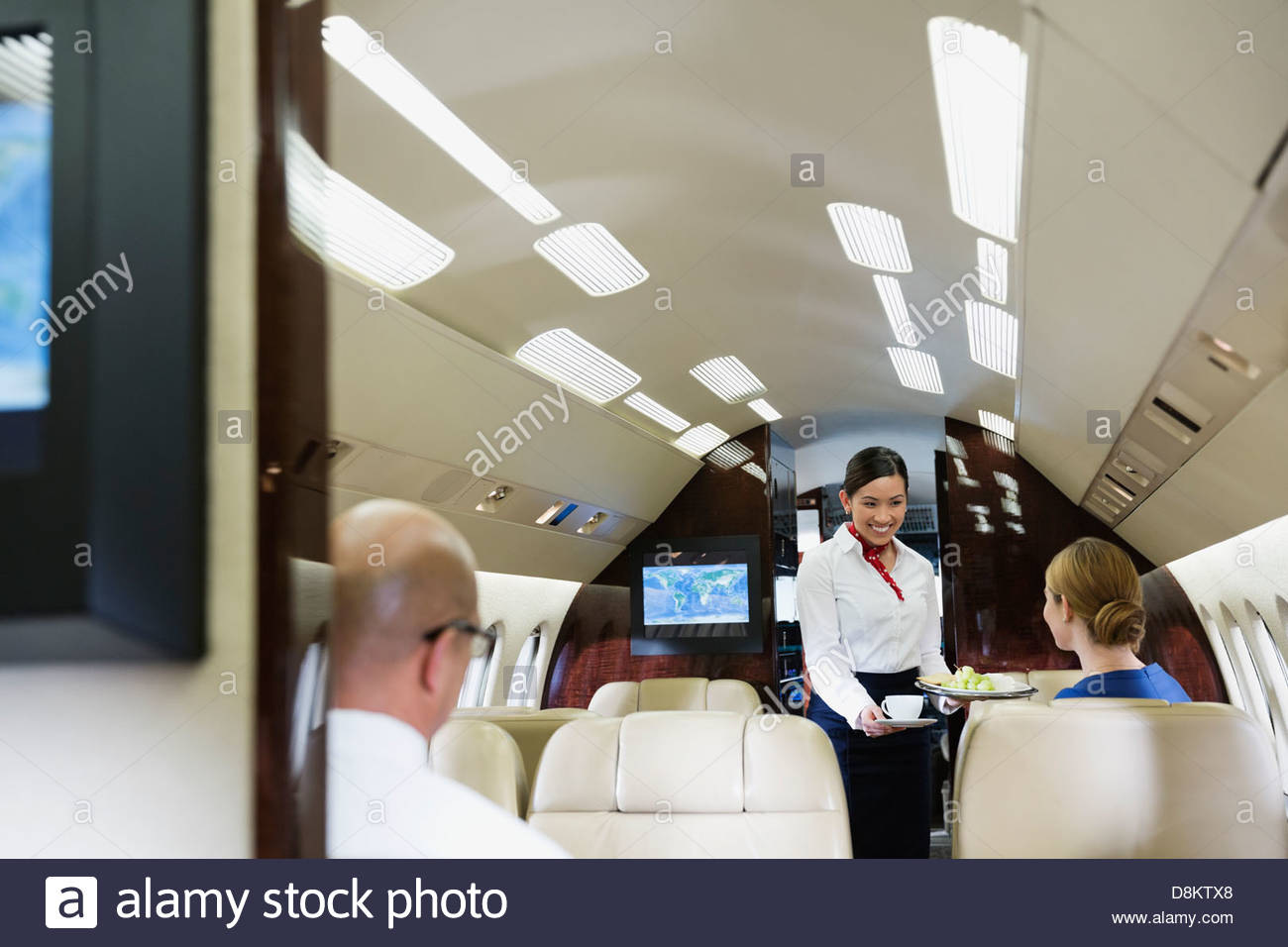 Flight attendant serving food to female passenger in airplane - Stock Image