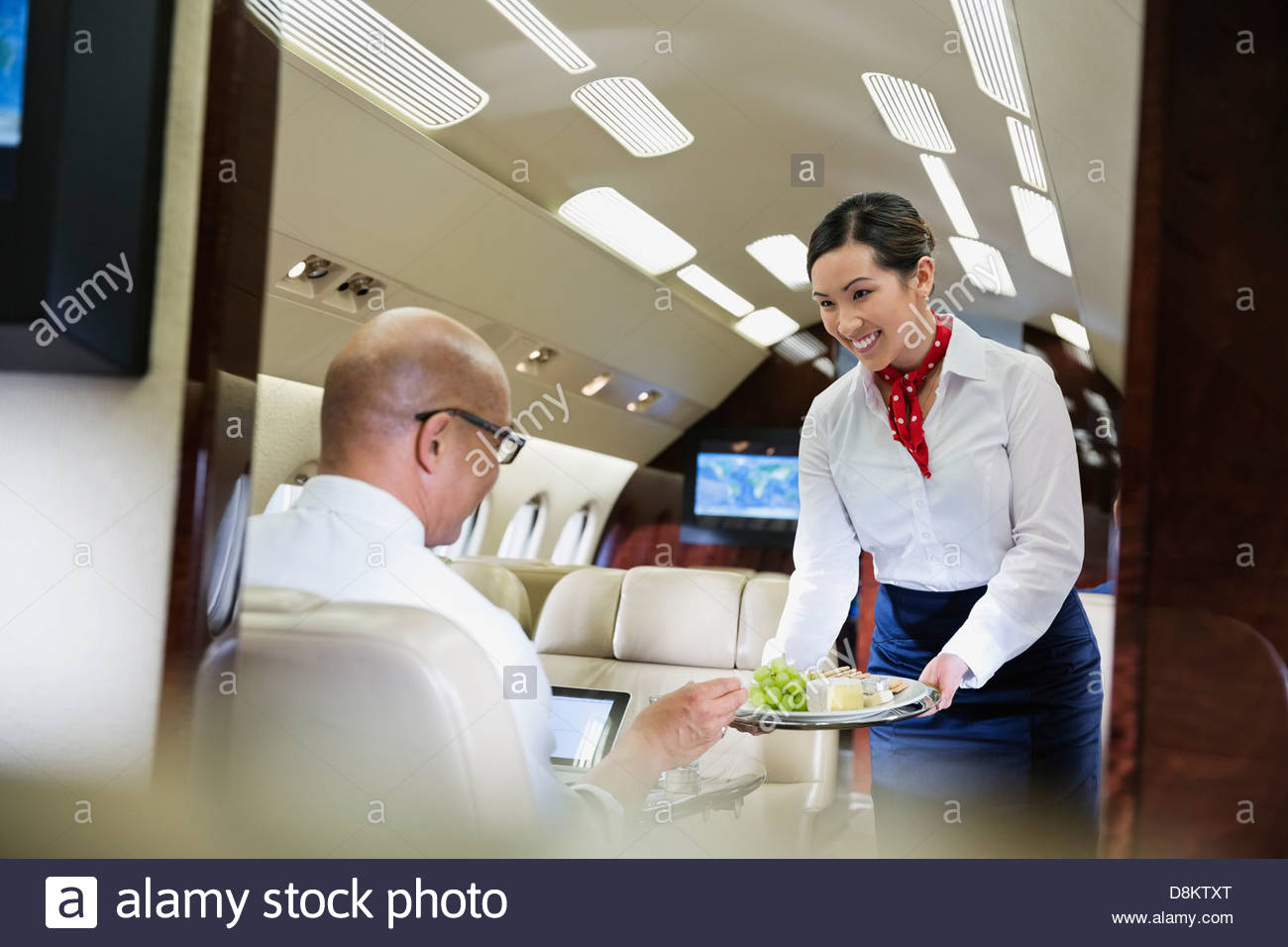 Flight attendant serving food to male passenger in airplane - Stock Image