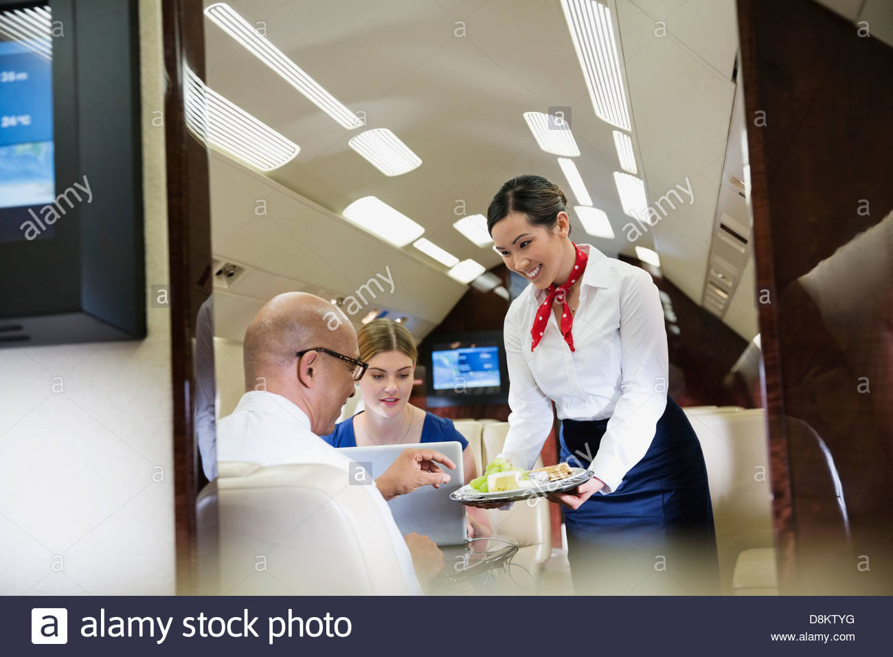 Flight Attendant Serving Food To Business Colleagues In