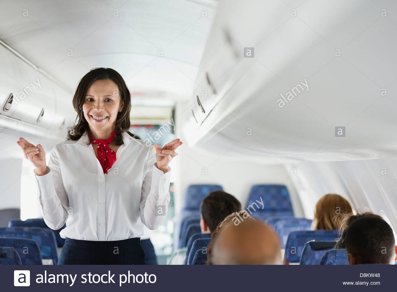 Flight attendant indicating exits in airplane - Stock Image