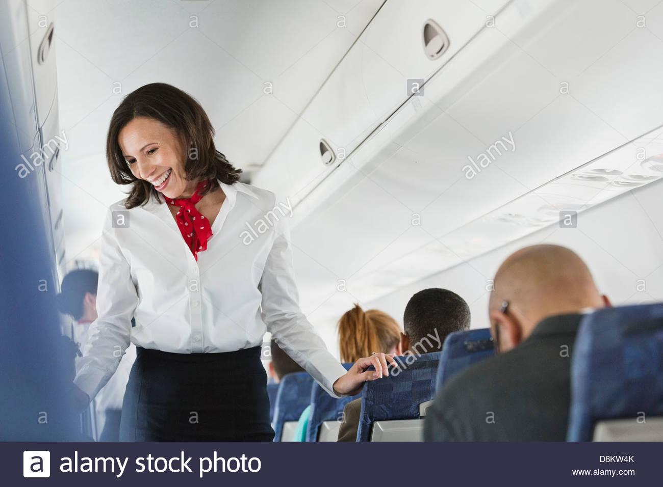 Flight attendant talking to passengers in airplane - Stock Image