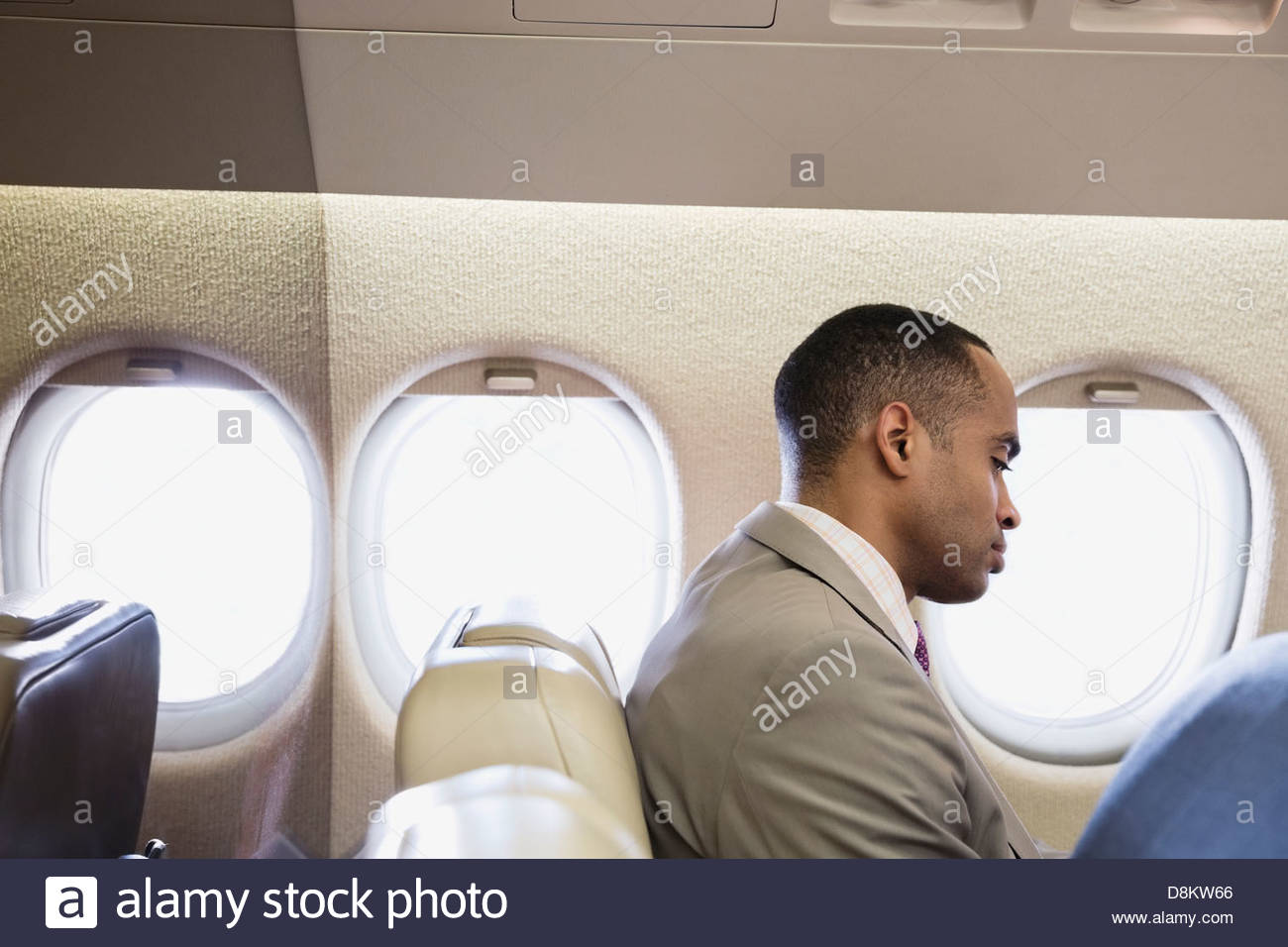 Businessman traveling in airplane - Stock Image