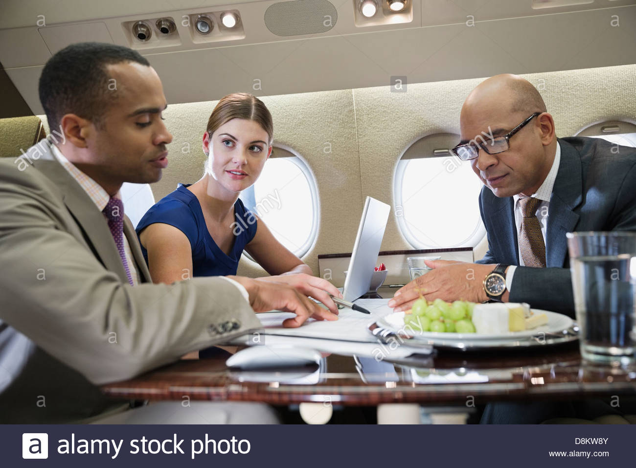 Business people working in private jet - Stock Image