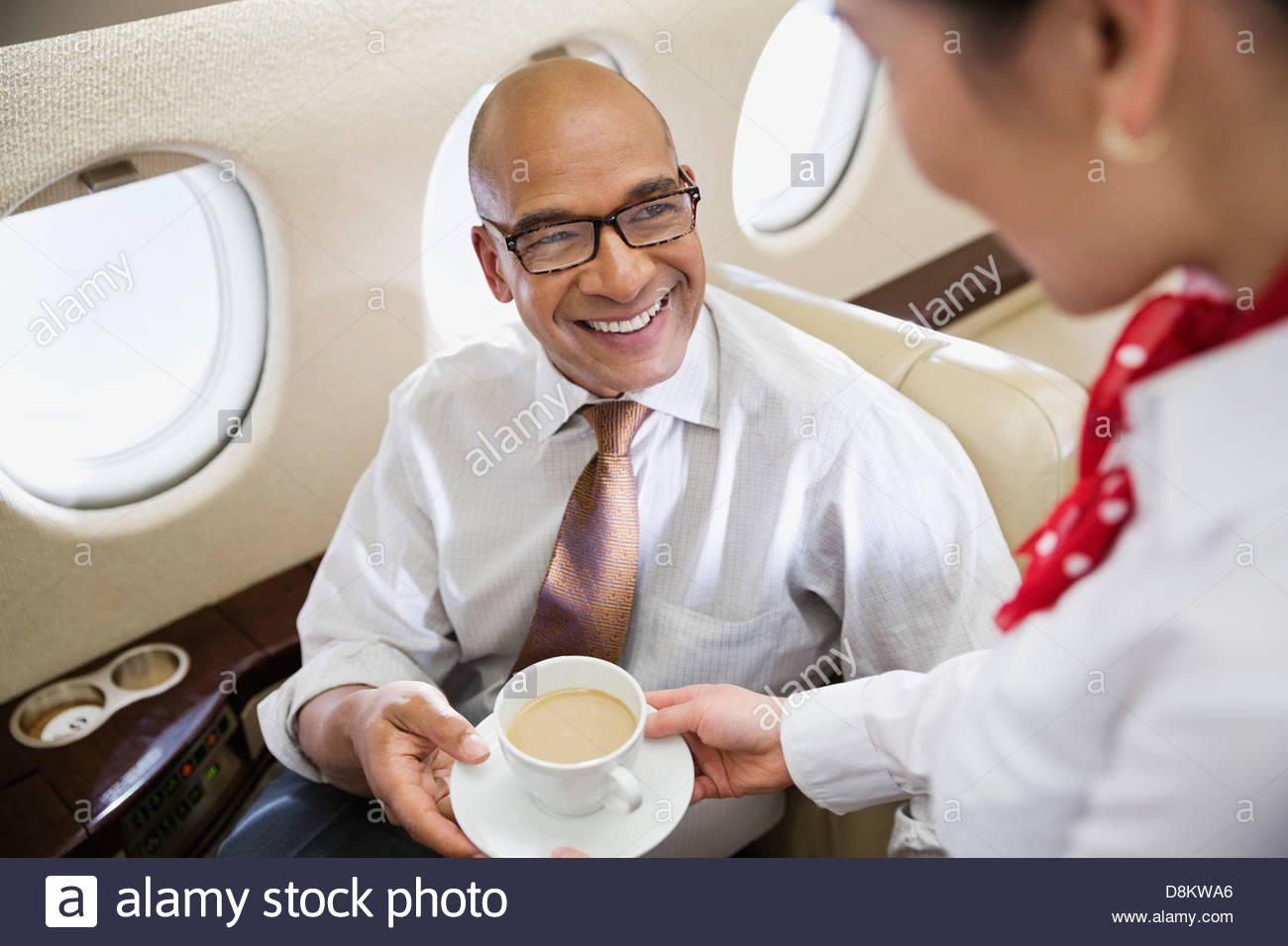 Flight attendant serving coffee to businessman in private jet - Stock Image