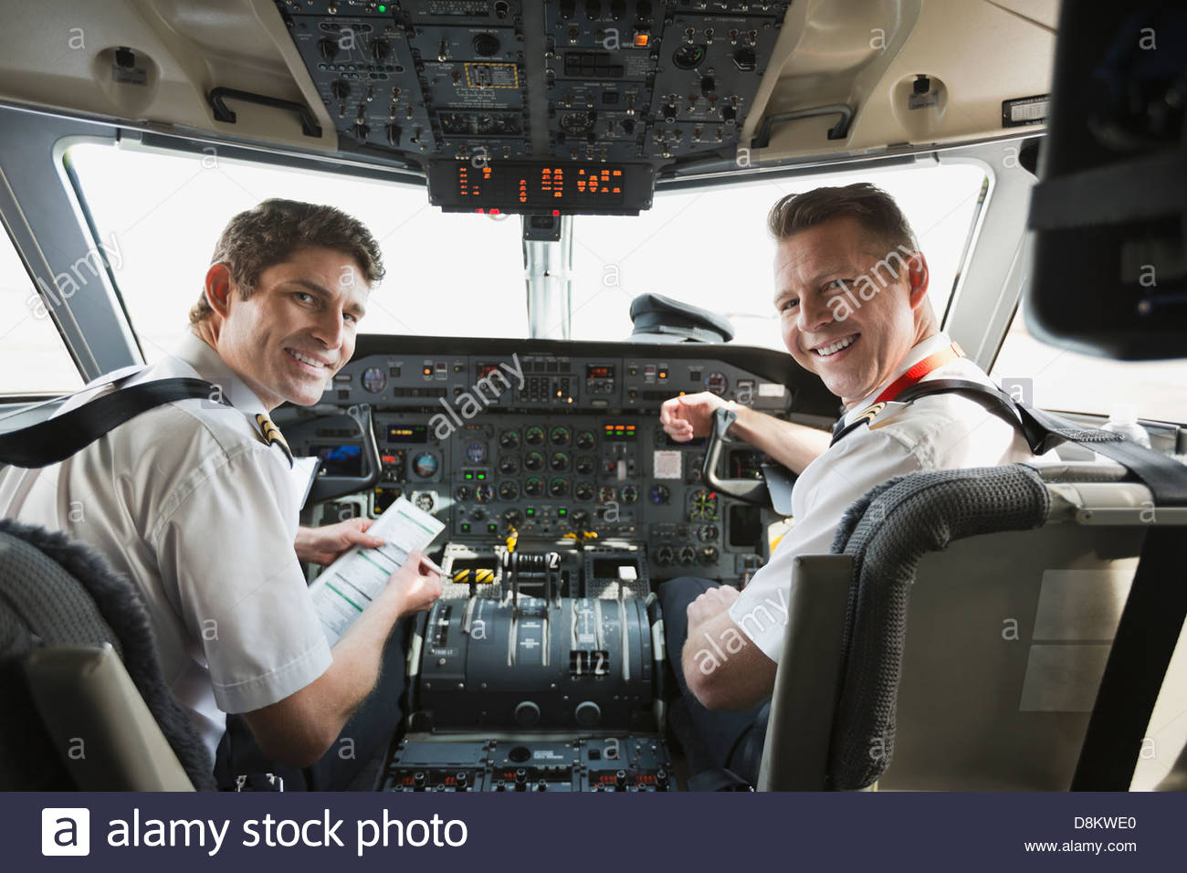 Portrait of male pilot and co-pilot in airplane cockpit - Stock Image