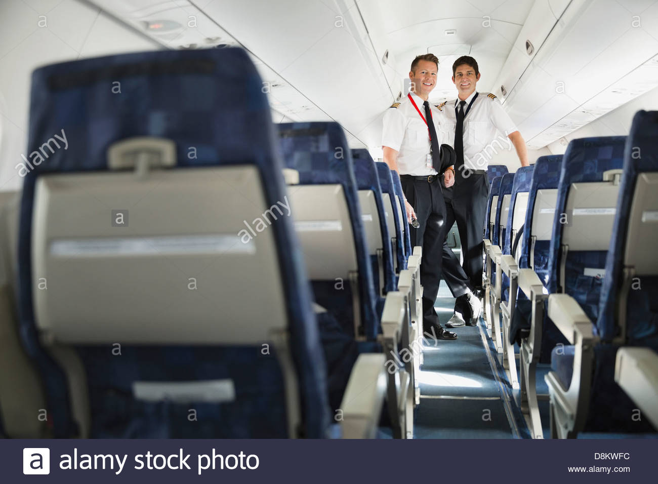 Portrait of male pilot and co-pilot standing in airplane cabin - Stock Image