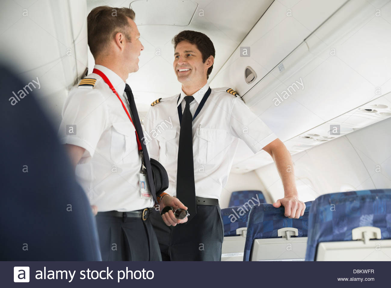 Male pilot and co-pilot talking in airplane cabin - Stock Image