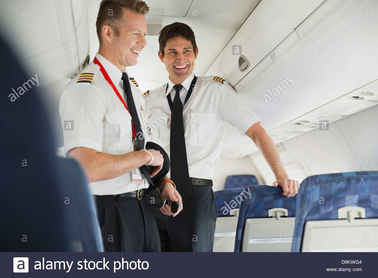 Smiling male pilot and co-pilot standing in airplane cabin - Stock Image