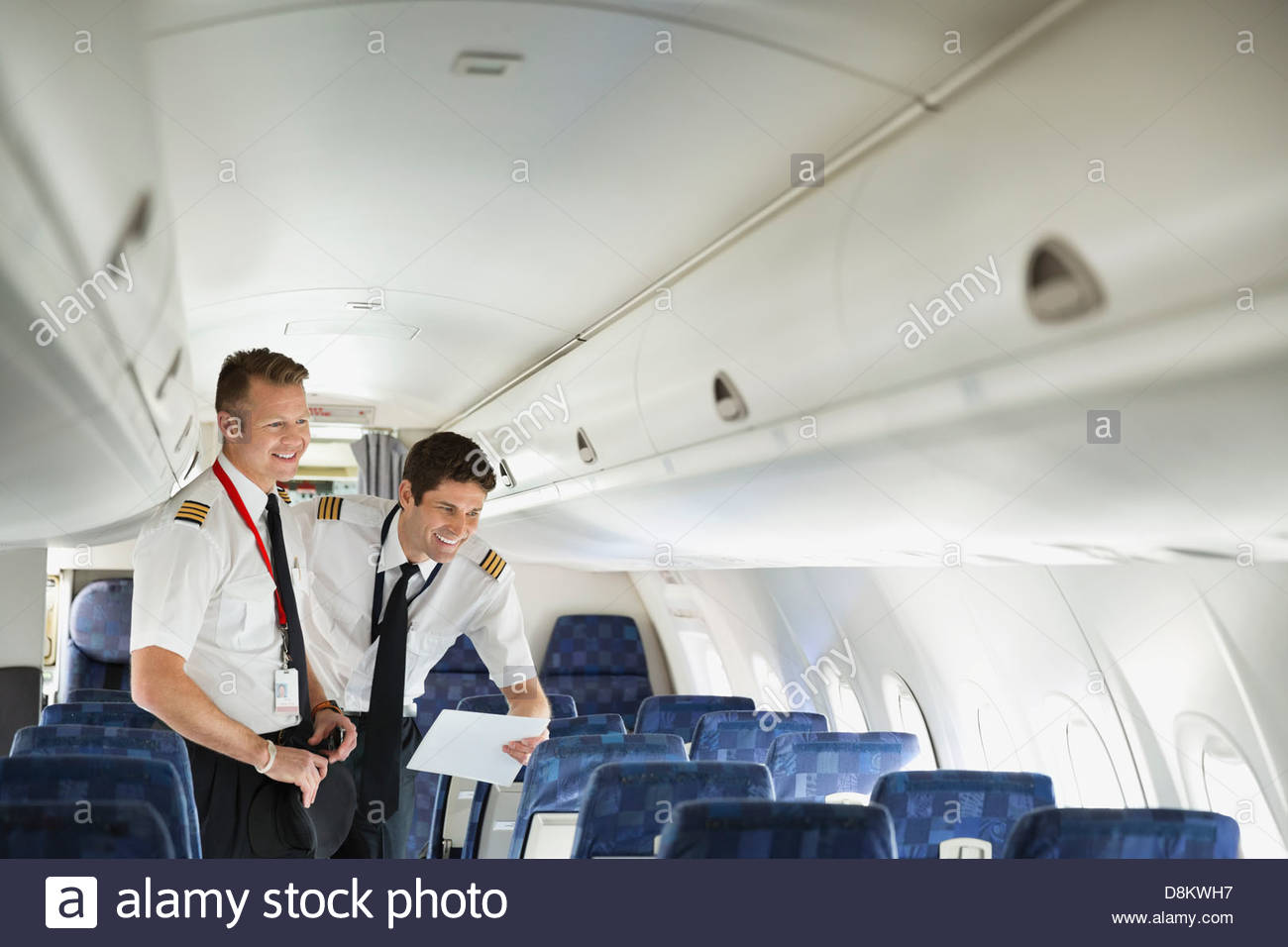 Male pilot and co-pilot looking out window in airplane cabin - Stock Image